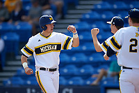 Michigan Wolverines designated hitter Drew Lugbauer (17) fist bumps teammates after scoring a run during the first game of a doubleheader against the Canisius College Golden Griffins on June 20, 2016 at Tradition Field in St. Lucie, Florida.  Michigan defeated Canisius 6-2.  (Mike Janes/Four Seam Images)