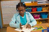 MR / Schenectady, New York. Yates Arts-in-Education Magnet School (urban public school). First grade classroom. Student (girl, 6) reads book at free reading time. MR: Cov1. ID: AM-g1w. © Ellen B. Senisi.
