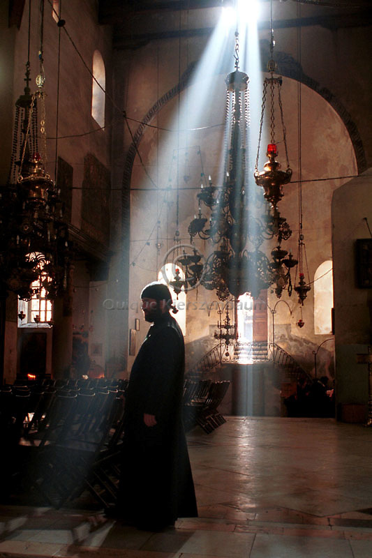 A Greek-Orthodox priest is highlighted by Sunday morning sunbeams inside the Church of the Nativity December 17, 2000 in the West Bank city of Bethlehem.
