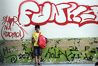 Pictured: A young migrant boy stands by a graffiti on his first day at school at the Thissio 72nd Primary School of Athens Greece. Monday 10 October 2016<br /> Re: Children of refugees have started school in various parts of Greece.