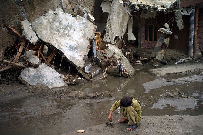 A boy plays with mud in front of ruins in a flood damaged neighborhood of Mingora, Swat valley, Pakistan, on Aug. 26, 2010.