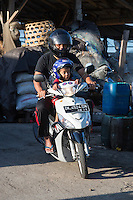 Jimbaran, Bali, Indonesia.  Father and Son on Motorbike, with Helmets.