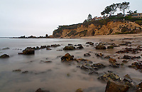 A thick marine layer blocks the sun and provides the perfect setting for a long-exposure shot of the beach and houses on the bluffs above Little Corona just after sunset.  The pathway down to the beach from the street parking is visible underneath the trees on the right, as is the often-closed lifeguard tower.  A sole person can be seen sitting on the lifeguard tower, looking out over the ocean.