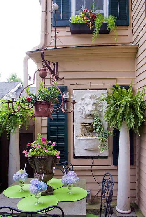 """Small patio garden with house, shade, garden furniture, pot containers, ornaments, hydrangea """"ice cream"""", windowboxes, columns with ferns, adorable relics and flea market finds."""