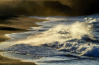 Waves crash on the black sand beach of Kiholo Bay, sending mist into the air, Kohala, Big Island of Hawai'i.