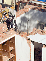 Laborers manually demolish a house in Bangalore, Karnataka, India