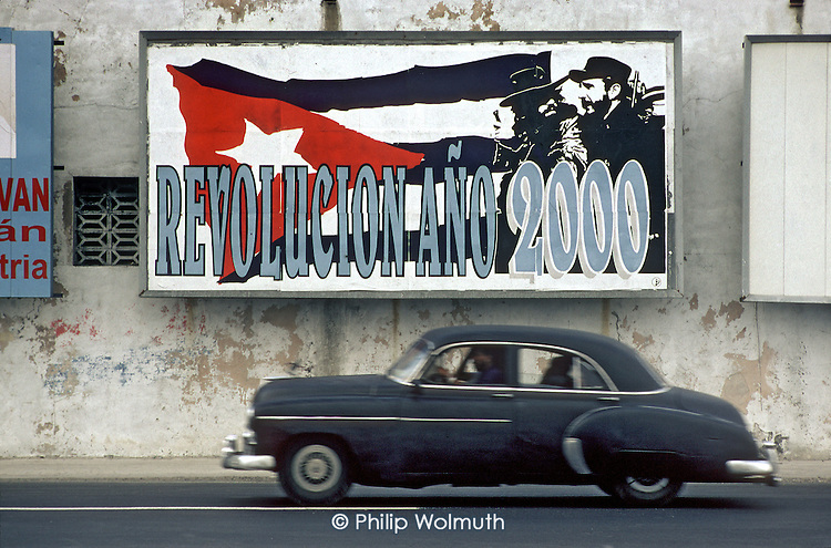An ageing American car passes beneath a roadside hoarding marking the anniversary of the Cuban revolution