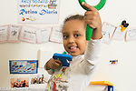 Education Preschool 3 year olds happy girl portrait holding up magnifying glass as she holds foam letters