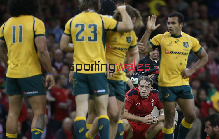 A dejected Cory Allen at the final whistle as the Australian players celebrate victory over Wales.<br /> Dove Men Series 2014<br /> Wales v Australia<br /> Millennium Stadium<br /> 08.11.14<br /> ©Steve Pope-SPORTINGWALES