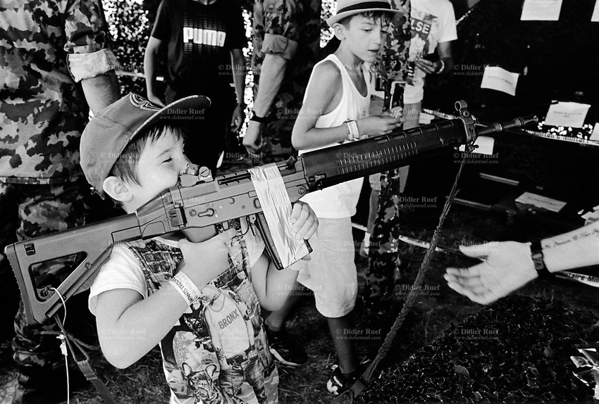 """Switzerland. Canton Fribourg. Estavayer. A young boy is playing with an automatic or semi-automatic assault rifle <br /> SG 550 at a swiss army stall during the Federal Wrestling and Alpine Games Festival. The SG 550 is an assault rifle manufactured by Swiss Arms AG (formerly Schweizerische Industrie Gesellschaft) of Neuhausen, Switzerland. """"SG"""" is an abbreviation for Sturmgewehr, or """"assault rifle"""". The rifle is based on the earlier 5.56mm SG 540 and is also known as the Fass 90 or Stgw 90. An assault rifle is a selective-fire rifle that uses an intermediate cartridge and a detachable magazine. 27.08.2016  © 2016 Didier Ruef"""