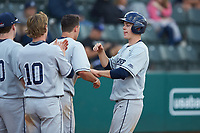 Chris Givin (35) of the Xavier Musketeers is greeted by his teammates after scoring a run during the game against the Penn State Nittany Lions at Coleman Field at the USA Baseball National Training Center on February 25, 2017 in Cary, North Carolina. The Musketeers defeated the Nittany Lions 7-5 in game two of a double header. (Brian Westerholt/Four Seam Images)