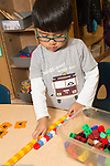 Education preschool 3-4 year olds boy using manipulatives comparing length of two towers of cubes he made from different colors