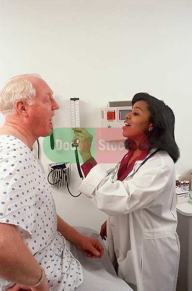 Physician checks throat of mature patient
