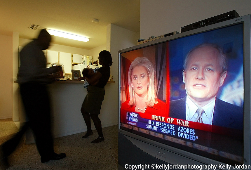 News about impending war with Iraq plays on the televsion as Sgt. Rickey Moore, left, and his wife Theresa, holding their five month-old son Timothy as they prepare for church Sunday morning, March 16, 2003 at their Port Orange home.(Kelly Jordan)..**FOR DEPLOYMENT GALLERY**