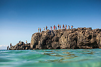 Beachgoers walk on the famous (and dangerous) Jump Rock at Waimea Bay, O'ahu.