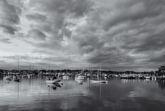 Dramatic clouds at sunrise over sunlit sailboats and other pleasure craft moored in the harbor shortly after sunrise in Oak Bluffs, Massachusetts on Martha's Vineyard.