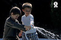 Two boys (11-13) playing with garden hose, smiling (Licence this image exclusively with Getty: http://www.gettyimages.com/detail/sb10065145bn-001 )