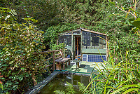 BNPS.co.uk (01202 558833)<br /> Pic: Symonds&Sampson/BNPS<br /> <br /> Solar panels provide electricity.<br /> <br /> £125,000 - For your own idyllic rustic hideaway...<br /> <br /> Fancy the unique chance to own a remote woodland shack in its own private valley near Lyme Regis in Dorset?<br /> <br /> The timber chalet, with a pond, decking and a log bridge across a stream, is buried in the middle of 10 acres of private woodland near the seaside resort.<br /> <br /> The primitive but eco-friendly chalet can be slept it overnight but can't be used as a permanent residence.