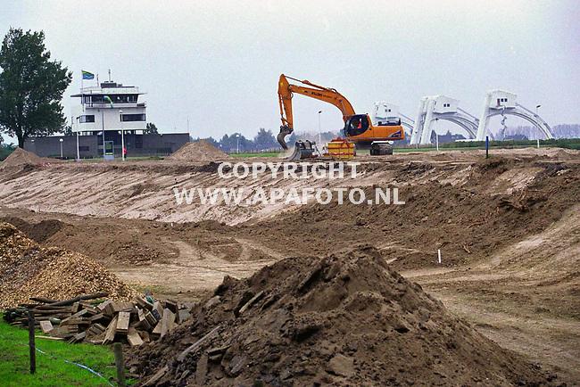 Doorwerth,22-10-99  Foto: Koos Groenewold (APA)<br />Deze week is  in het kader van het project` ruimte voor de rivier` in opdracht van Rijkswaterstaat  begonnen met de afgravingen in de uiterwaarden van Doorwerth.De toegangsweg naar het stuweiland wordt over de gehel lengte met 2 meter verlaagd.Volgend jaar komt het stuweiland aan de beurt dat op verschillende plaatsen 1 tot 11/2 meter zal worden afgegraven.Voor de werkzaamheden aan het stuweiland is ruim f 3 miljoen beschikaar.Het geld is afkomstig van ` Interregionale Rijn- en Maasactiviteiten.Dit is een Europees hoogwaterprogramma waarin wordt samengewerkt tussen Nederland,Duitsland,Belgie,Frankrijk en Luxemburg.Doel van deze samenwerking is om de overlast van hoogwater tegen te gaan.Door het eiland en de toegangsweg te verlagen stroomt het water er bij hoogwater er sneller overeen waardoor het waterpeil zakt.<br />In totaal zijn er 7 van deze projecten,waarvan 4 in Duitsland en 3 in Nederland( Overijssel) Driel / Doorwerth  is echter verreweg het grootste project) Het karwei zal pas in 2001 worden afgerond.