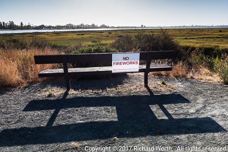 """""""No Fireworks"""" sign on a bench at the MLK Regional Shoreline where grass along the shoreline and into the salt marsh is summer dry."""