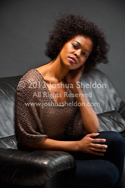 Young African American woman sitting on sofa