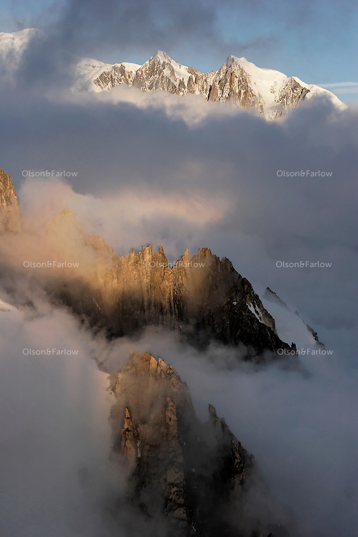 Needle with No Name and other craggy peaks in the foreground with Mont Blanc rising 4807 meters above the ground shrouded in morning fog and clouds in the background..