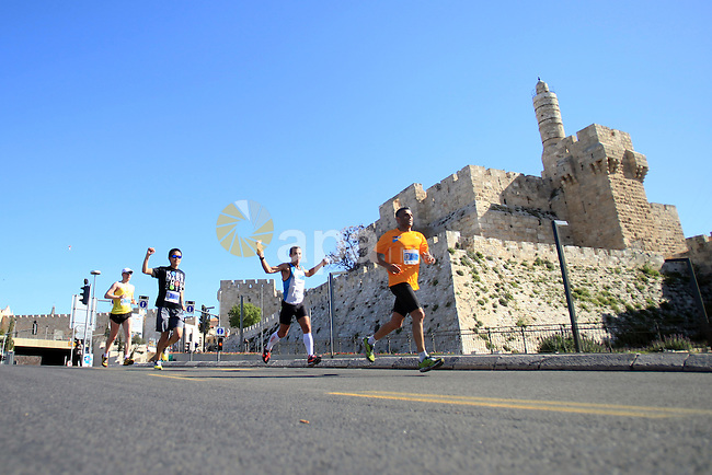 Local and international runners take part in the annual Jerusalem Marathon in the Old City on March 21, 2014. More than 15,000 runners from 50 different countries participated in the annual sporting event included running tracks for full and half marathons which passed through a section of Jerusalem's Old City. Photo by Saeed Qaq