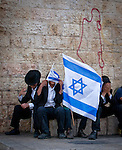 Ultra Orthodox Jews cover them selves  with the Israeli flag outside Damascus gate in Jerusalem Wednesday May 28 2014, during festivities  marking Jerusalem day. The Day marks the reunification of Jerusalem following the 1967 Six Day War when Israel captured the Arab part of the city from Jordan. Photo By Eyal Warshavsky