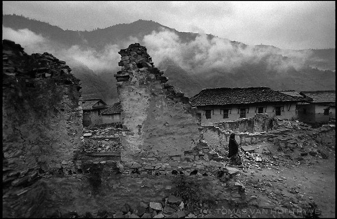 A villager walks among ruins of buildings bombed by the Royal Nepal Army when they raided the village of Thabang, the capital of Nepal's Maoist held areas on 20 June, 2005.<br />