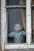 A child looks out the window of his home in Uelen, eastern Russia