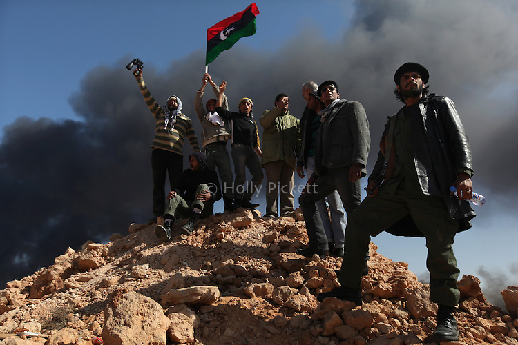 Opposition rebels chant in front of a large plume of black smoke from an oil refinery in Ras Lanuf, Libya, March, 11, 2011. Loyalist forces of Col. Muammar Qaddafi pushed rebels back from the strategic oil town with air strikes, artillery and small arms fire.