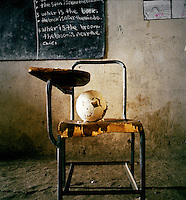 'Where is the ball? The ball is on the chair' A classroom in Chimbiri school...Children take turns in putting objects on the chair, while the teacher writes on the blackboard. The teachers learn English themselves at school before attending college, yet many are poorly trained. The young teachers in this school tend to stay for a year then move on, depending on the decisions taken by the government. In remote schools such as this one, teachers stay in the local village and travel home at weekends...