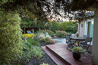 Secluded small space deck in the shade of trees behind home; Lundstrom Garden, design by Susan Morrison