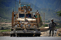 US soldier from RCP29 (103rd Mountain Division - Route Clearance Patrol), stands guard  outside a Huskie MRAP on a paved road in the Kunar Valley near the Pakistan border.