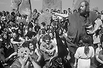 1970's style hippies attend the second  free festival at Stonehenge to celebrate the summer solstice June 21st 1979. Hippy woman wearing a mask celebrate the sun god Belenus. Chief Hippy known as the King of the Hippies Sid Rawle sprinkles the group with water as a blessing.