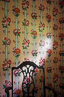 Back of wooden chair in front of floral wallpaper<br />