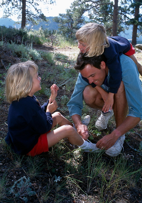 A father and his daughters having fun while tying a shoe along a trail in Rocky Mtn Nat'l Park, CO