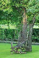 """Les jardins du prieuré d'Orsan :  """"le verger de pommiers"""" avec pommiers de plein vent et un fauteuil en baguettes de bois le long d'un poirier<br /> <br /> Mention obligatoire du nom du jardin et pas d'usage publicitaire sans autorisation préalable."""