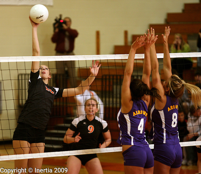 SIOUX FALLS, SD - OCTOBER 13:  Mercede Stotesbery of Washington tips the ball past Tia Hemiller #4 and Rainey Mack #8 of Watertown in the third game of their match Tuesday night at Washington. (Photo by Dave Eggen/Inertia).