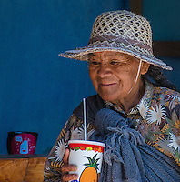 Urban Street Photograph of elderly Mexican lady in Sayulita Mexico, enjoying her first sip of a tropical fruit shake.