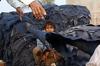 A child worker sits amongst piles of leather outside a tannery in the Jajmau area of Kanpur.