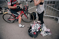Danilo Wyss (SUI/BMC) getting supplied by a sponsor at the stage start (with an exploding goodies-bag nearby)<br /> <br /> 104th Tour de France 2017<br /> Stage 7 - Troyes › Nuits-Saint-Georges (214km)