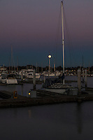 Moon rise, the Full Buck Moon, rising through shades of blue and purple, among sailboats moored at the San Leandro Marina on San Francisco Bay.