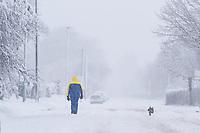 A man walks his dog in the snow in the village of Redbourn, Hertfordshire, UK. Sunday 10 December 2017.