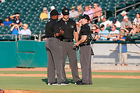 Umpires (left to right) Dexter Kelley, Dillon Wilson and Tyler Jones discuss a call during the game between the Mississippi Braves and the Tennessee Smokies at Smokies Stadium on July 15, 2021, in Kodak, Tennessee. (Danny Parker/Four Seam Images)