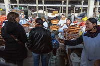 Peru, Cusco, San Pedro Market.  Women Selling Bread Clamoring for Attention of Potential Buyers.
