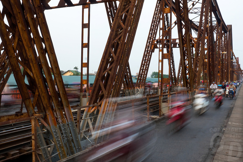 """Long Biên Bridge (Vietnamese: Cầu Long Biên) is a historic cantilever bridge across the Red River that connects two districts, Hoan Kiem and Long Bien of the city of Hanoi, Vietnam. It was originally called Paul Doumer Bridge.<br /> <br /> The bridge was built in 1899-1902 by the architects Daydé & Pillé of Paris, and opened in 1903.Before North Vietnam's independence in 1954, it was called Paul-Doumer Bridge, named after Paul Doumer - The Governor-General of French Indochina and then French president. At 1.68 kilometres (1.04mi) in length, it was, at that time, one of the longest bridges in Asia. For the French colonial government, the construction was of strategic importance in securing control of northern Vietnam. From 1899 to 1902, more than 3,000 Vietnamese took part in the construction.<br /> It was heavily bombarded during Vietnam War due to its critical position (the only bridge at that time across the Red River connecting Hanoi to the main port of Haiphong). The first attack took place in 1967, and the center span of the bridge was felled by an attack by 20 USAF F-105 fighter-bombers. CIA reports noted that the severing of the bridge did not appear to have caused as much disruption as had been expected. The defence of Long Bien Bridge continues to play a large role in Hanoi's self-image and is often extolled in poetry and song. It was rendered unusable for a year when, in May 1972, it fell victim to one of the first co-ordinated attacks using laser-guided """"smart bombs""""."""