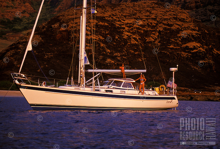 Mother and daughter relaxing on sailboat off Makua Beach, West Side Oahu