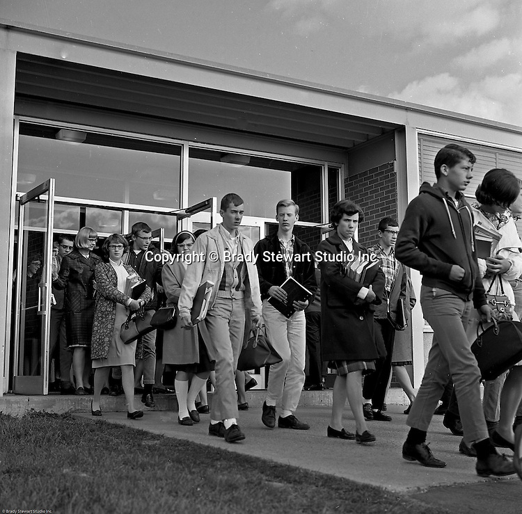 Bethel Park Senior High School:  View of students coming out of Building #1 between classes. The new Bethel Senior High School was dedicated on October 23, 1960, but the campus would not grow to its current size until seven years later. Phase II of the construction was completed in 1964 with the addition of another academic building and the industrial arts building. Phase III was completed in 1967 with the construction of the fourth academic building and a 6,300 seat football stadium and track, three tennis courts, seven basketball courts, and a baseball field.