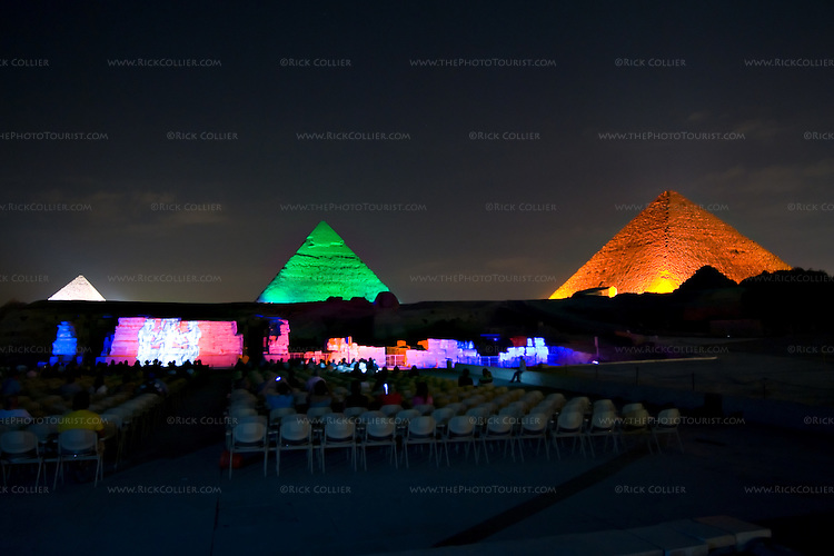 """Giza, Cairo, Egypt -- The three famous pyramids at Giza, surrounded by the """"queen's pyramids"""" and with the remains of the funerary temple of Khafre (Khephren) (featuring the Great Sphinx) are spectacularly illuminated during the famous sound and light show at Giza. © Rick Collier / RickCollier.com."""